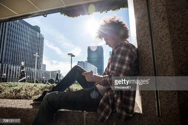 Young man sitting on wall in backlight looking at cell phone
