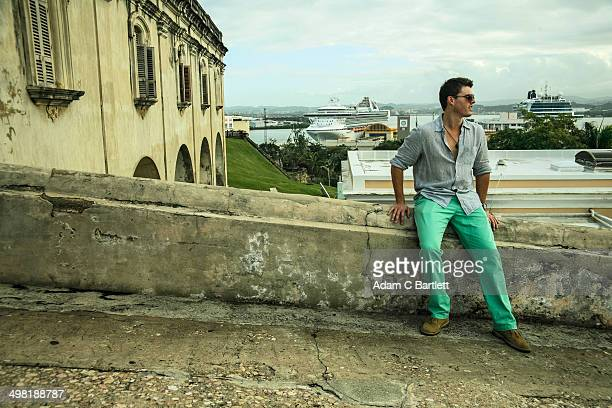 young man sitting on wall next to castillo san felipe del morro, old san juan, puerto rico - old san juan wall stock photos and pictures
