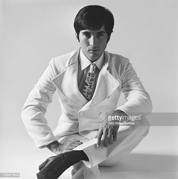 Young man sitting on white background, portrait