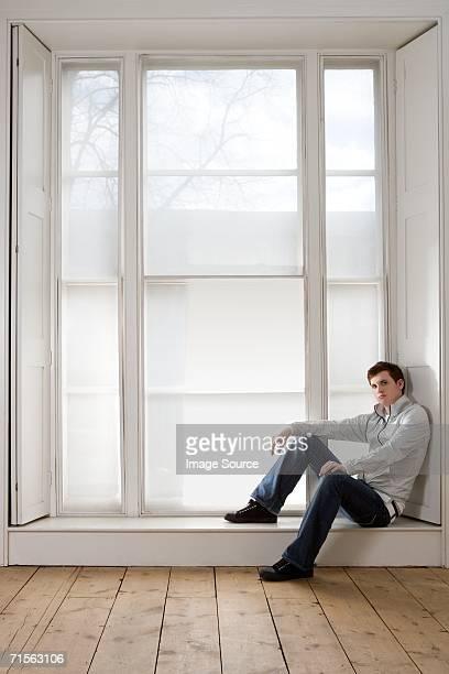 若い男性が座ってウィンドウの縁