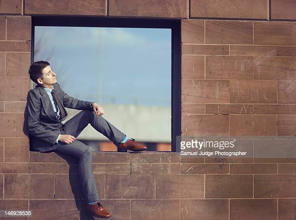 Young man sitting on window