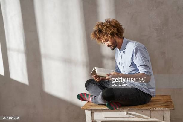 Young man sitting on wooden table reading book