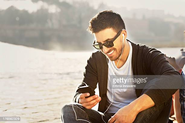 Young man, sitting, outdoor, sunny, mobile phone