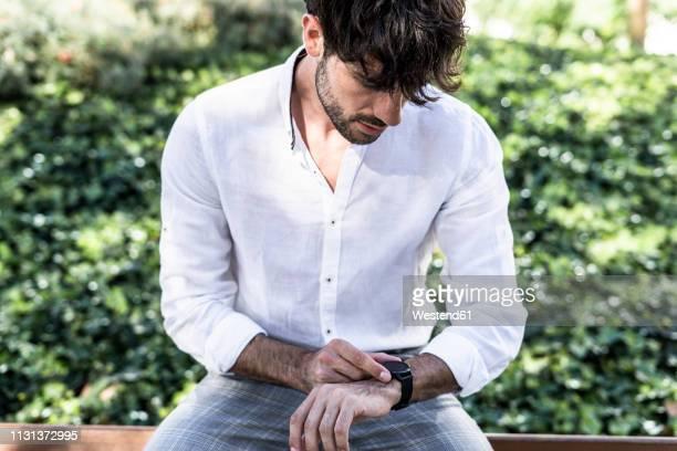 young man sitting outdoors using smartwatch - armbanduhr stock-fotos und bilder