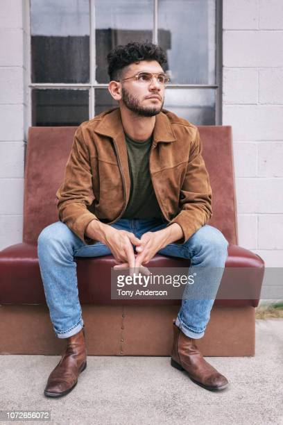 young man sitting outside building - sitting foto e immagini stock