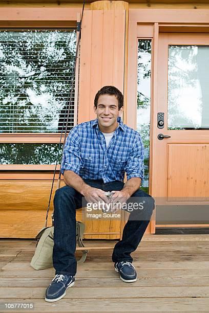 Junger Mann sitzt vor log cabin