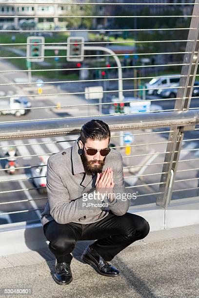young man (hipster style) sitting over a walk-bridge - pjphoto69 stockfoto's en -beelden