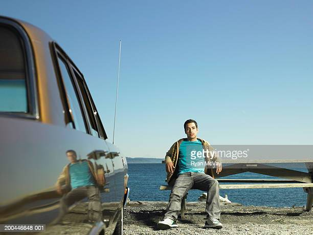 Young man sitting picnic table beside parked car, sea in background