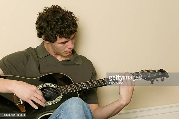 Young man sitting, playing acoustic guitar
