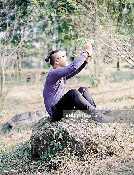 Young Man Sitting Rock At Field And Clicking Selfie