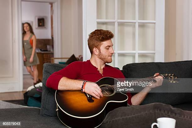 Young man sitting sofa playing guitar