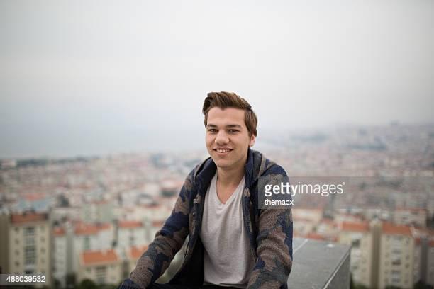 Jeune homme assis avec vue sur la ville