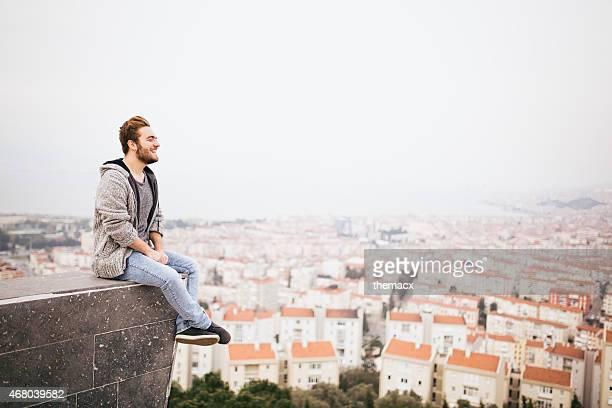Joven hombre sentado con el paisaje de la ciudad