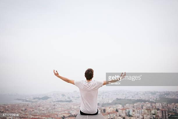 Junger Mann sitzt mit Blick auf die Stadt