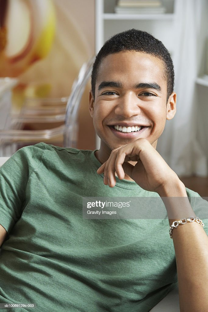 Young man sitting with hand on chin, smiling, portrait : Stockfoto