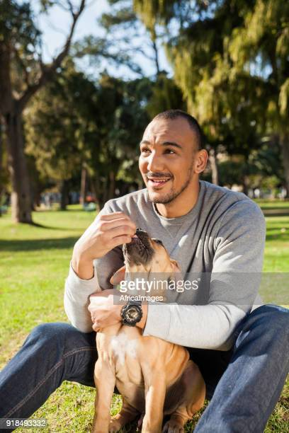 Young man sitting with his dog on the grass in the park.