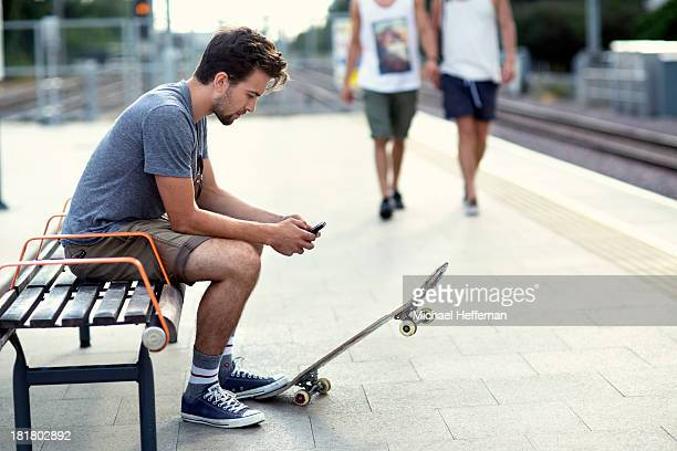 Young man sitting with mobile phone and skateboard