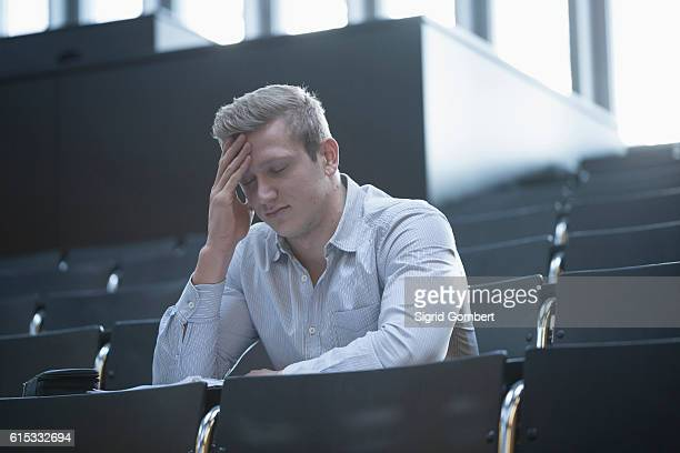 young man sitting with tension in lecture hall with head in hands, freiburg im breisgau, baden-württemberg, germany - sigrid gombert stock pictures, royalty-free photos & images