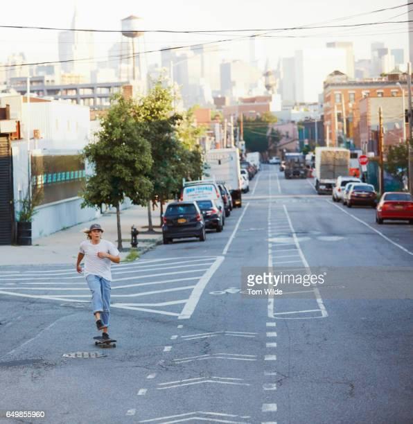 young man skateboarding in an empty street in brooklyn, new york - 白tシャツ ストックフォトと画像