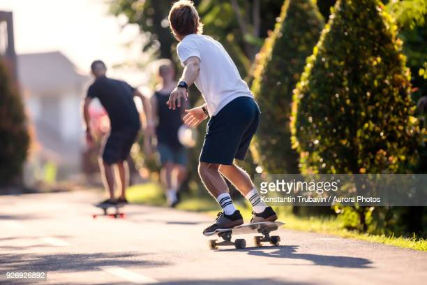 young man skateboarding in street, canggu, bali, indonesia - longboard skating stock pictures, royalty-free photos & images