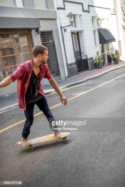 Young man skateboarding on city street