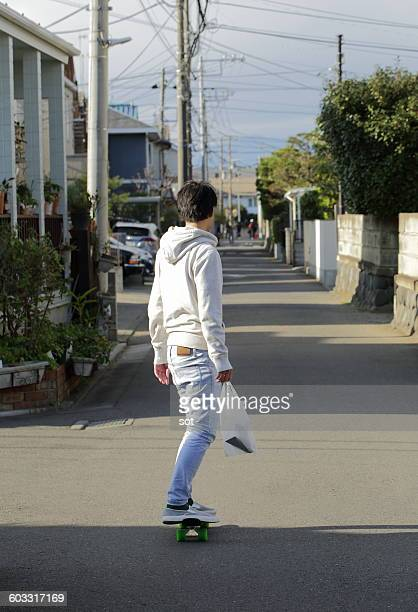 Young man skateboarding on the road