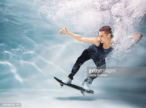 Young man skateboarding underwater