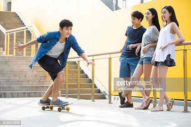 Young man skateboarding with friends