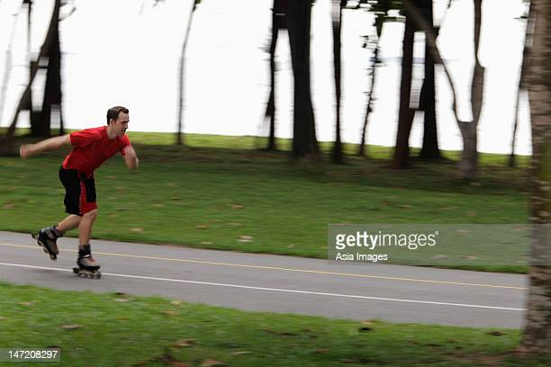 young man skating through park