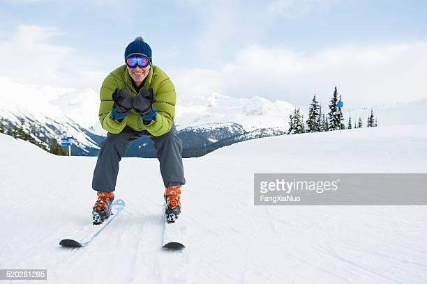 Young man skiing down ski slope and smiling, front view