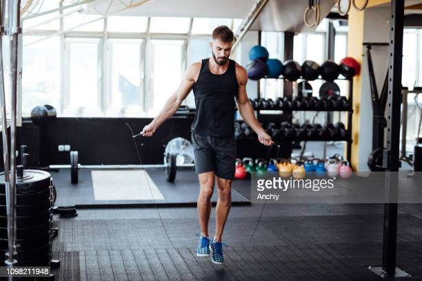 young man skipping rope in the gym - skipping along stock photos and pictures