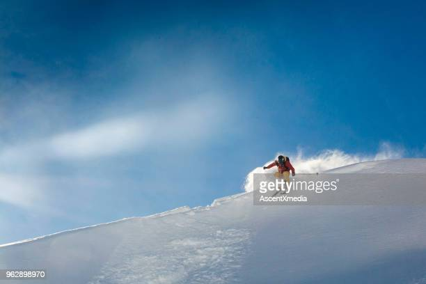 young man skis off corniced ridge in powder snow - freezing motion photos stock pictures, royalty-free photos & images