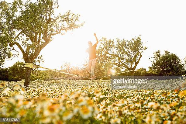 Young man slacklining over flower field, Mallorca, Balearic Islands, Spain
