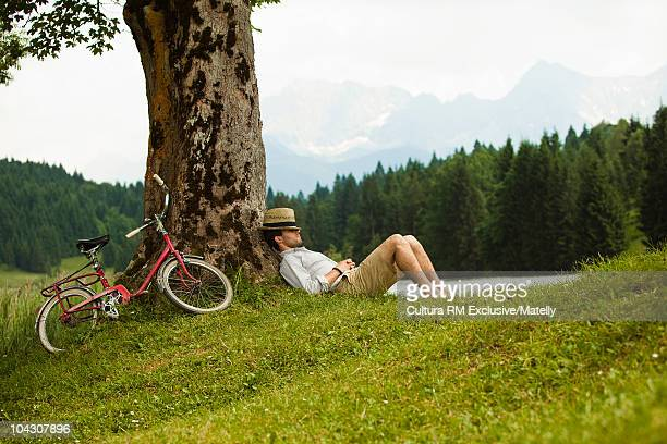 Young man sleeping against a tree