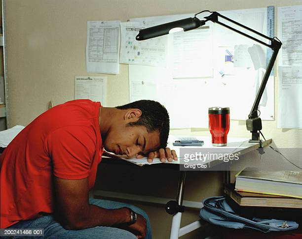 Young man sleeping  at desk, side view
