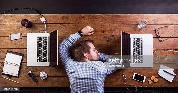 Young man sleeping at work, power napping