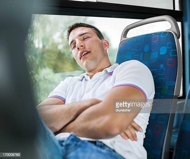 Jeune homme dormant dans un bus.