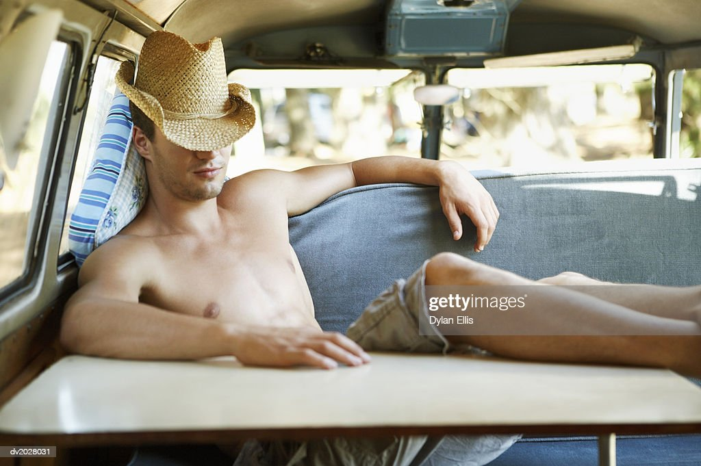 Young Man Sleeping in a Motor Home With His Feet Up on a Table : Stock Photo