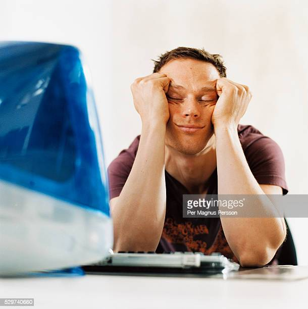 Young man sleeping in front of computer