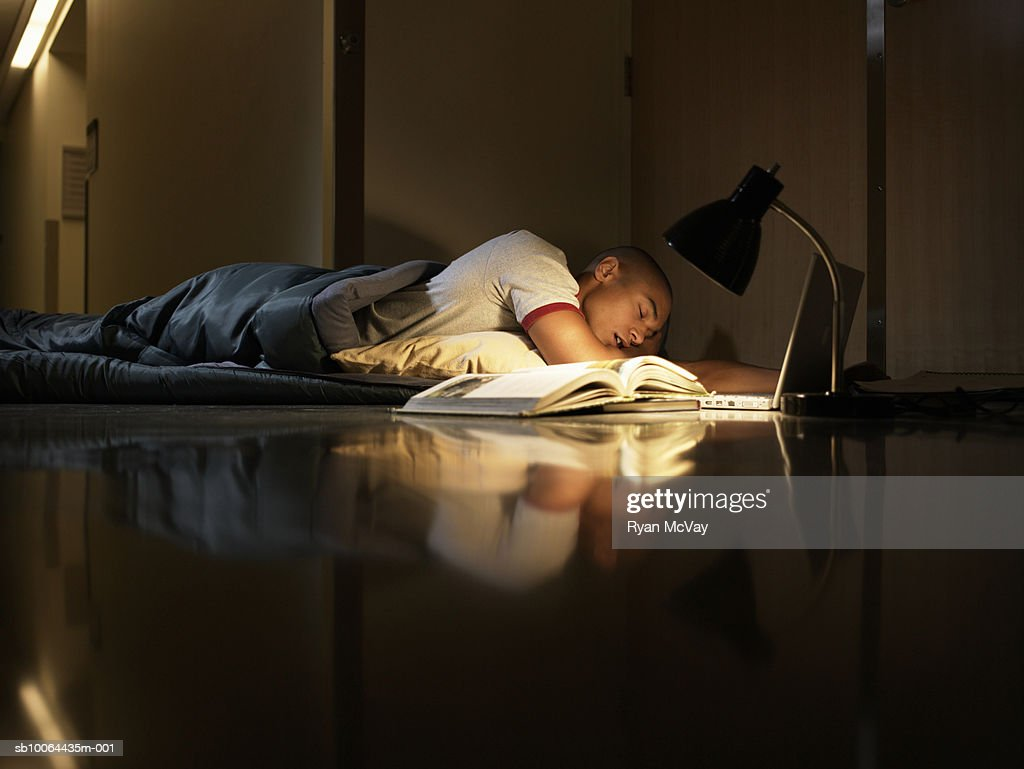 Young man sleeping in sleeping bag on floor with lamp, laptop and open book : Stock Photo