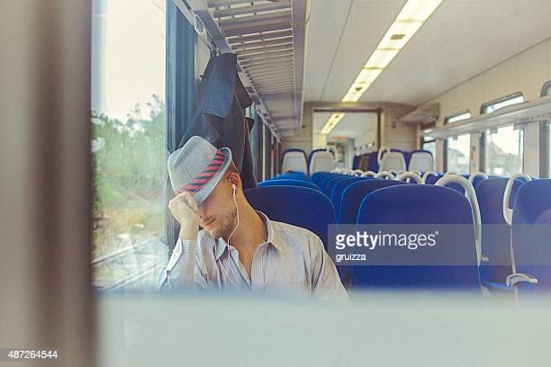 Junger Mann schlafen im Zug, während die Fahrt zur Arbeit