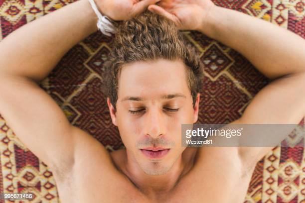 Young man sleeping on carpet