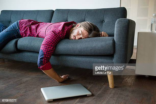 young man sleeping on sofa with laptop - lying down foto e immagini stock
