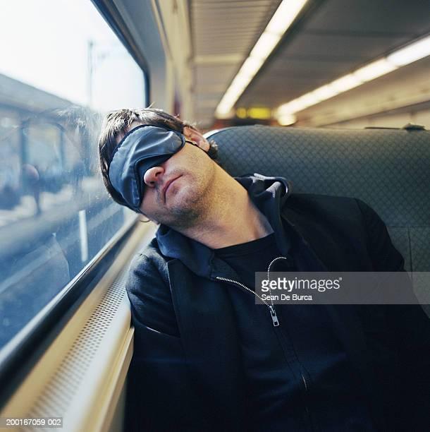 Young man sleeping on train