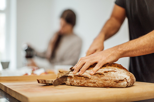Young man slicing bread on cutting board in kitchen - gettyimageskorea