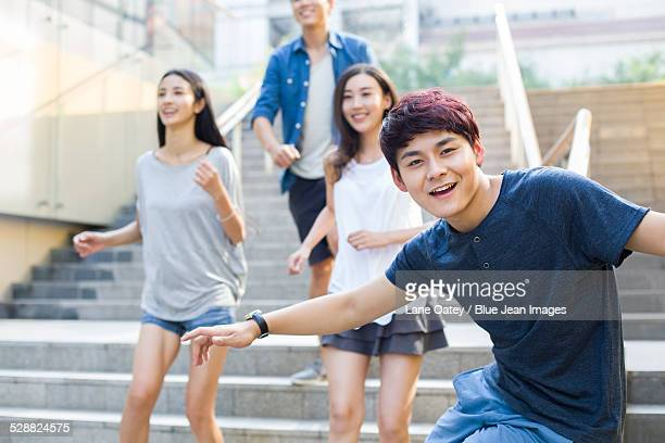 Young man sliding down banister on steps