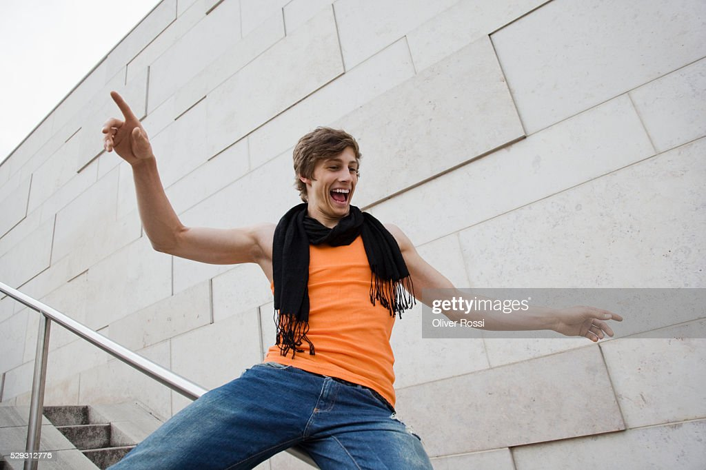 Young man sliding down railing : Stock Photo