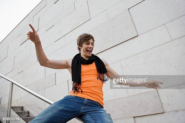 Young man sliding down railing