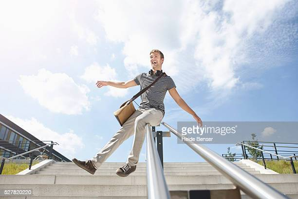 young man sliding on handrail - sliding stock pictures, royalty-free photos & images