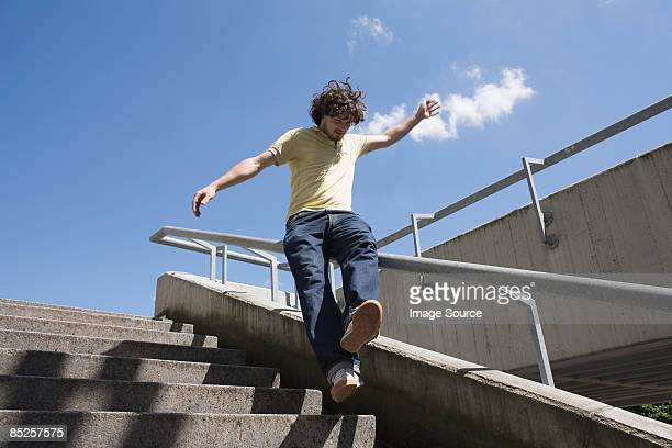 young man sliding on railings - veiligheidshek stockfoto's en -beelden